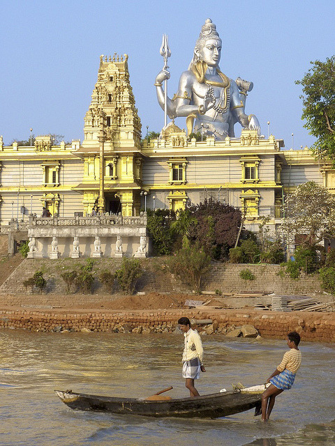 Fishermen taking out under the watchful eye of Shiva in Murudeshwara, Karnataka, India